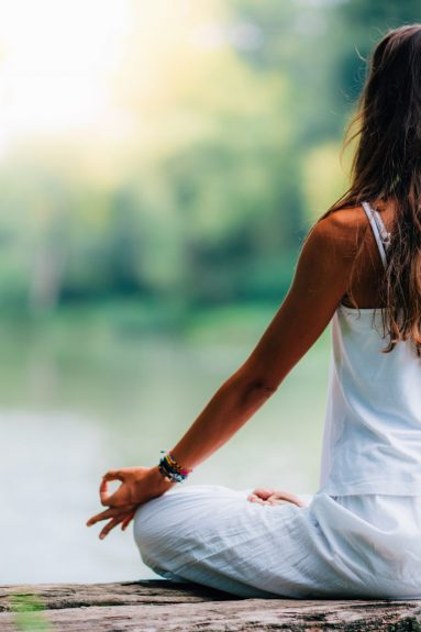 Woman doing yoga by the lake, sitting in lotus pose with fingers in mudra position.